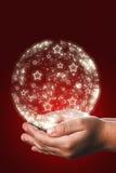 Cartão de Natal com mãos de uma criança no vermelho Fotos de Stock Royalty Free