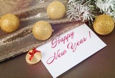 Cartão de Natal com um sinal, um ramo do abeto vermelho na neve, bolas do ouro Fotos de Stock