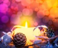 Cartão de Natal com vela, os botões spruce e o cenário no bokeh foto de stock