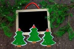 Cartão de Natal a decoração do Natal entregou árvores de Natal do feltro com estrelas vermelhas, as estrelas de brilho e o quadro Fotos de Stock Royalty Free