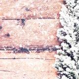 Cartão de Natal do vintage com a árvore de abeto coberta com a neve em de madeira Foto de Stock