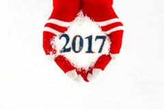 Cartão de Natal, luvas nas mãos que guardam a neve e 2017 anos novos mim Imagens de Stock Royalty Free