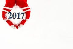 Cartão de Natal, luvas nas mãos que guardam a neve e 2017 anos novos mim Fotografia de Stock Royalty Free