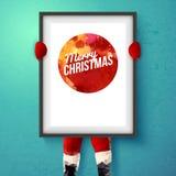 Cartão de Natal Santa está guardando um quadro com cumprimentos do feriado ilustração do vetor