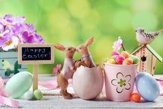 Cartão de Páscoa com beijo de coelhos e de decorações no backg da mola Fotos de Stock Royalty Free
