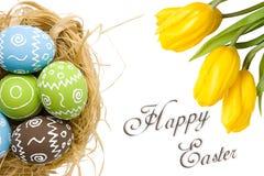 Cartão de Páscoa com os ovos coloridos no ninho e as tulipas amarelas sobre o fundo branco Vista superior com espaço da cópia fotos de stock royalty free