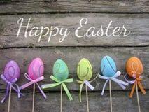Cartão de Páscoa com os ovos no fundo de madeira Imagens de Stock