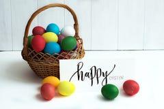 Cartão de Páscoa com ovos da páscoa coloridos em um ` feliz da Páscoa da cesta e do ` caligráfico da inscrição Fotografia de Stock Royalty Free