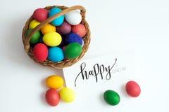 Cartão de Páscoa com ovos da páscoa coloridos em um ` feliz da Páscoa da cesta e do ` caligráfico da inscrição Fotos de Stock Royalty Free