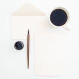 Cartão de papel da caligrafia com caneca, tinta e pena de café no fundo branco Configuração lisa, vista superior Imagem de Stock