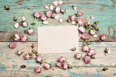 Cartão de papel vazio com as rosas cor-de-rosa pequenas na turquesa de madeira velha Fotos de Stock