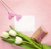 Cartão de papel vazio com tulipas, corações e a caixa de presente brancos em rosado Fotografia de Stock