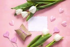 Cartão de papel vazio com tulipas, corações e a caixa de presente brancos em rosado Imagens de Stock Royalty Free