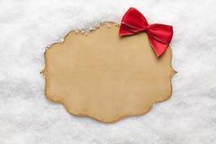Cartão de papel vazio e curva vermelha na neve Fotografia de Stock