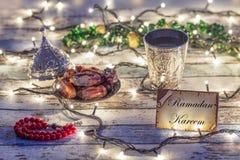 Cartão de Ramadan Kareem com datas, rosário, e copo da água com escrita de Allah no árabe foto de stock