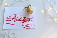 Cartão de rotulação com feriados do texto no escarlate da cor no shee branco Imagens de Stock Royalty Free