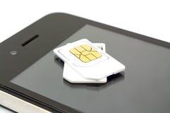 Cartão de Sim e telefone esperto no fundo branco Fotos de Stock Royalty Free