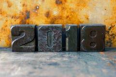 cartão de um projeto industrial de 2018 anos Dígitos artísticos coloridos no fundo oxidado do metal Cartaz retro do xmas do proje foto de stock royalty free