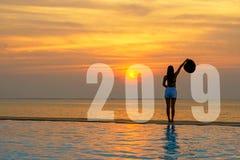 Cartão 2019 do ano novo feliz da mulher do estilo de vida Relaxamento e liberdade da mulher da silhueta na piscina perto do mar e foto de stock royalty free