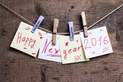 Cartão do ano novo feliz na superfície de madeira Fotografia de Stock