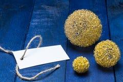 Cartão do convite com as bolas douradas do deco na madeira azul Imagem de Stock