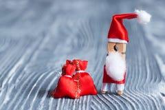 Cartão do convite do Feliz Natal O Peg engraçado Santa do pregador de roupa do brinquedo com presente vermelho ensaca no fundo de Fotografia de Stock Royalty Free
