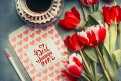 Cartão do dia de mães com o texto que rotula a melhor mamã nunca, os corações e o lápis, tulipas bonitas e xícara de café Fotos de Stock