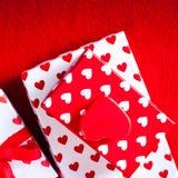 Cartão do dia de Valentim com caixas de presente e corações no vermelho sentido para trás Imagem de Stock