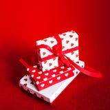 Cartão do dia de Valentim com caixas de presente e corações no vermelho sentido para trás Fotos de Stock Royalty Free