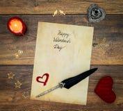 Cartão do dia de Valentim do vintage com coração vermelho do afago, decorações de madeira, cervo pintado, vela e tinta vermelha e fotografia de stock royalty free