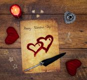 Cartão do dia de Valentim do vintage com corações vermelhos do afago, cervos pintados, vela e tinta vermelha e pena no carvalho d imagens de stock royalty free