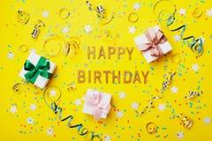 Cartão do feliz aniversario com confetes, presente ou caixa e serpentina atuais na opinião superior do fundo amarelo estilo liso  Imagem de Stock Royalty Free