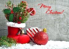 Cartão do Feliz Natal Cartão do Xmas A bota vermelha do ` s de Santa com ramo de árvore do abeto, baga decorativa do azevinho sae Fotos de Stock Royalty Free