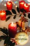 Cartão do Feliz Natal com texto Velas, caixas de presente e ramo do Lit do azevinho imagens de stock royalty free