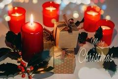 Cartão do Feliz Natal com texto Velas, caixas de presente e ramo do Lit do azevinho imagens de stock