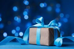 Cartão do feriado Caixa de presente ou presente do Natal com a fita da curva no fundo mágico do bokeh de turquesa Fotografia de Stock Royalty Free