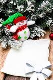 Cartão do Natal com a árvore vermelha da bola e de Natal, boneco de neve no fundo de madeira Vista superior Fotos de Stock
