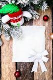 Cartão do Natal com a árvore vermelha da bola e de Natal, boneco de neve no fundo de madeira Vista superior Imagem de Stock Royalty Free