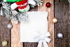 Cartão do Natal com a árvore vermelha da bola e de Natal, boneco de neve no fundo de madeira Vista superior Fotos de Stock Royalty Free