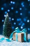 Cartão do Natal com efeito do bokeh Árvore e caixa de presente de abeto no fundo da neve Foto de Stock