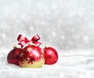 Cartão do Natal e do ano novo com as bolas vermelhas na neve e no espaço para o texto Fotos de Stock Royalty Free