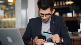 Cartão do smartphone e de banco da terra arrendada do empresário que faz o pagamento em linha no café filme