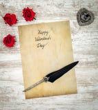 Cartão do vintage com as 3 rosas vermelhas, tintas e penas no carvalho pintado branco - vista superior fotografia de stock