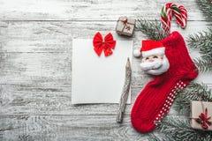 Cartão do Xmas Fundo de madeira, branco pintado com uma peúga do Natal e Santa Claus Árvore e doces de abeto coloridos neles Foto de Stock Royalty Free