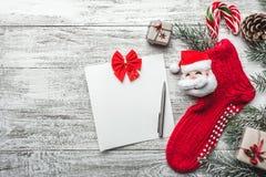 Cartão do Xmas Fundo de madeira, branco pintado com uma peúga do Natal e Santa Claus Doces coloridos neles Presente Handmade Fotografia de Stock