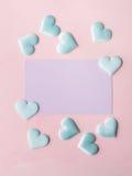 Cartão e corações pasteis roxos no fundo textured cor-de-rosa Fotos de Stock Royalty Free