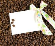 Cartão e curva brancos em um fundo de feijões de café Fotografia de Stock