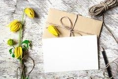 Cartão e envelope brancos vazios com as flores e o lápis amarelos do outono Fotos de Stock