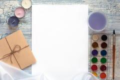 Cartão e envelope brancos vazios com velas, grânulos e pinturas da aquarela sobre a tabela rústica com espaço da cópia mock foto de stock royalty free