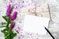 Cartão e envelope brancos vazios com wildflowers lilás Fotografia de Stock